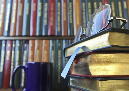 A Pair of Silver Glasses on a Stack of Leather Bound Books in a Library photo