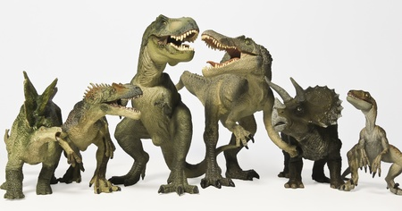 A Group of Six Ferocious Dinosaurs Lined Up in a Row Against White photo