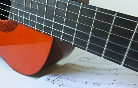 A Close Up of the Fingerboard of an Orange Classical Guitar and Sheet Music