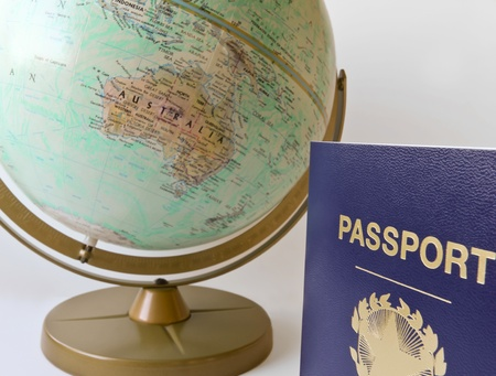 A Blue Passport and a World Globe Showing Australia Against White