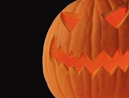 A Scary Halloween Jack-o-lantern Looms Against Black photo