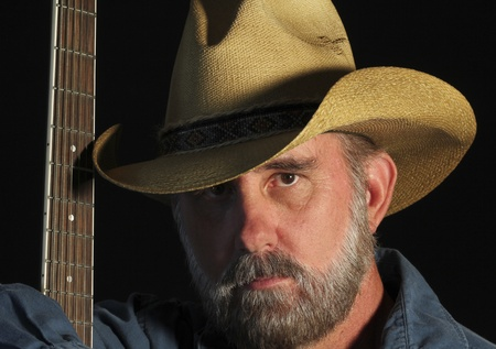 A Man with a Gray Beard Wears a Cowboy Hat and Holds a Guitar