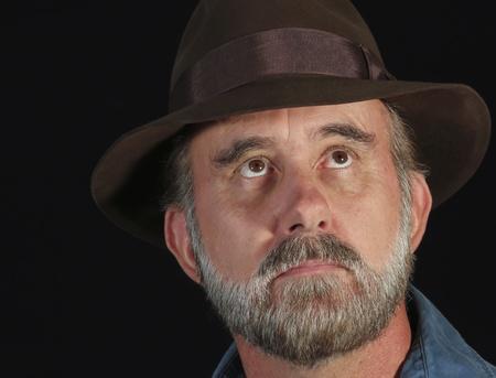 hombre con barba: Un hombre barbudo en un Fedora Miradas Hacia el cielo en la noche