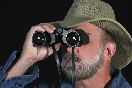 A Bearded Man in a Blue Shirt and Safari Hat Looks Through Binoculars photo