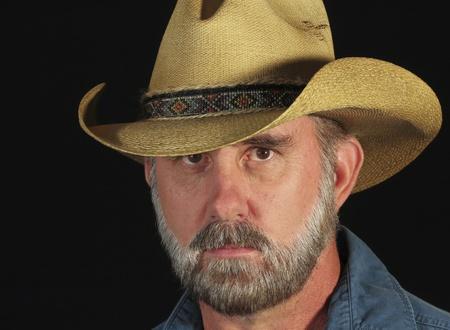 hombre con barba: Un hombre con los ojos marrones y una barba gris con un sombrero vaquero de paja con una banda con cuentas