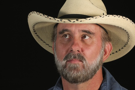 A Man with Brown Eyes and a Gray Beard in a White Straw Cowboy Hat