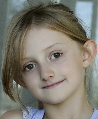 blond brown: A Portrait of an Ash Blonde Little Girl with Dark Hazel Green Eyes Stock Photo