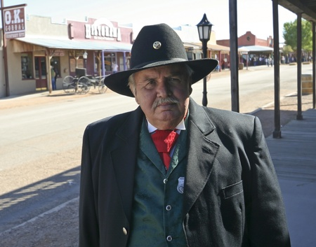 Tombstone, Arizona - October 22: Allen Street on October 22, 2011, in Tombstone, Arizona. A Helldorado participant dressed in period costume welcomes tourists to historic Allen Street where gunfights and barroom brawls are staged during this annual celebr