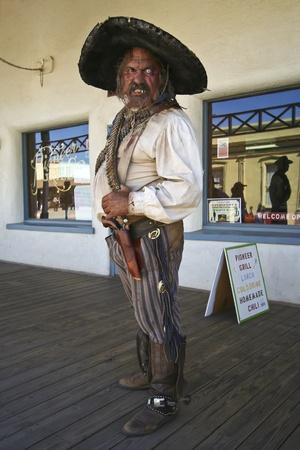 vestidos de epoca: Tombstone, Arizona - 22 de octubre: Allen Street el 22 de octubre de 2011, en Tombstone, Arizona. Un Bandolero Helldorado vestidos con trajes de �poca da la bienvenida a los turistas a la hist�rica Allen Street, donde los tiroteos y peleas de bar se celebran durante este a�o celebrando Editorial