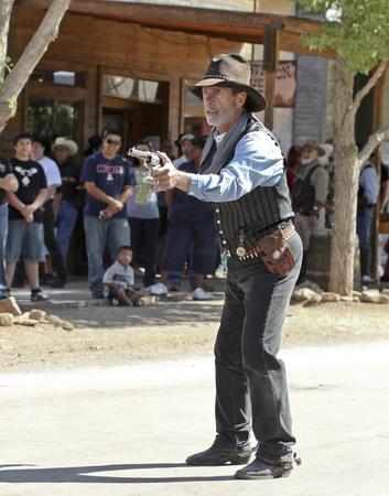 vestidos de epoca: Tombstone, Arizona - 22 de octubre: Allen Street el 22 de octubre de 2011, en Tombstone, Arizona. Un pistolero Helldorado vestidos con trajes de �poca lleva a cabo para los turistas en la hist�rica calle Allen, donde los tiroteos y peleas de bar se celebran durante este cel anual