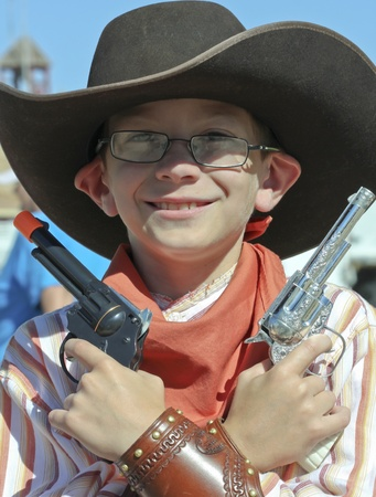 gunfights: Tombstone, Arizona - October 22: Allen Street on October 22, 2011, in Tombstone, Arizona. A Helldorado child participant dressed in period costume welcomes tourists to historic Allen Street where gunfights and barroom brawls are staged during this annual  Editorial