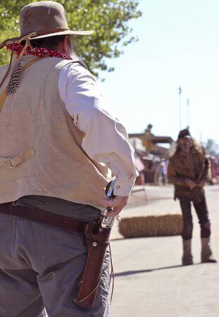 vestidos de epoca: Tombstone, Arizona - 22 de octubre: Allen Street el 22 de octubre de 2011, en Tombstone, Arizona. Un par de participantes Helldorado vestidos de pistoleros con trajes de �poca da la bienvenida a los turistas a la hist�rica Allen Street, donde los tiroteos y peleas de bar se organizan d
