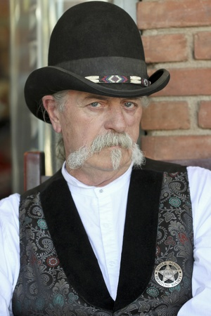 gunfights: Tombstone, Arizona - October 22: Allen Street on October 22, 2011, in Tombstone, Arizona. A Helldorado participant dressed in period costume welcomes tourists to historic Allen Street where gunfights and barroom brawls are staged during this annual celebr Editorial