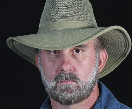 A Bearded Man in a Safari Hat Against a Black Background