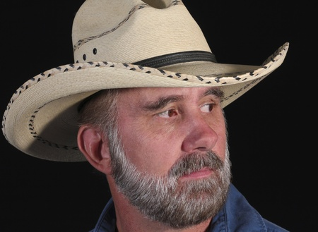 rugged: A Man with Brown Eyes and a Gray Beard in a White Straw Cowboy Hat