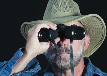 aged: A Bearded Man in a Blue Shirt and Safari Hat Looks Through Binoculars