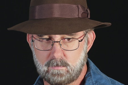 bearded wires: A Bearded Man in a Fedora and Silver Wire Framed Glasses Against a Black Background Stock Photo
