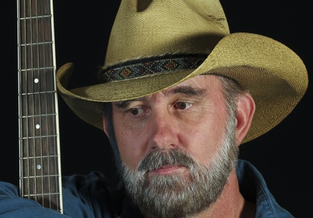 frets: A Man with a Gray Beard Wears a Cowboy Hat and Holds a Guitar