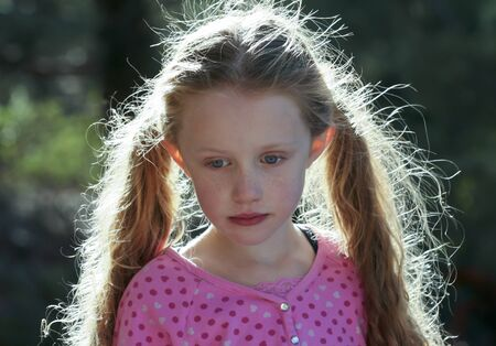 A Portrait of a Little Blonde Girl with a Pink Top and Backlit Hair photo