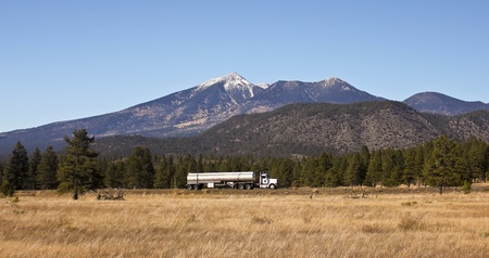 A Semi Tanker Truck Rolls Along with the San Francisco Peaks Rising in the Background photo
