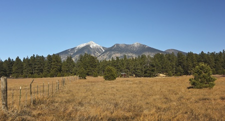 mount humphreys: An Old Barb Wire Fence with the San Francisco Peaks Rising in the Background Stock Photo