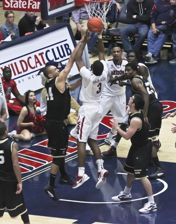 layup: TUCSON, ARIZONA - DECEMBER 22: MCKALE ARENA on DECEMBER 22, 2011, in TUCSON, ARIZONA. The University of Arizona Wildcats vs. Bryant. A contested layup by Kevin Parrum.
