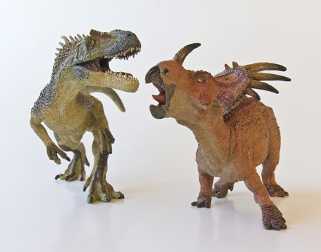 duel: Allosaurus and Styracosaurus battle it out against a white background Stock Photo