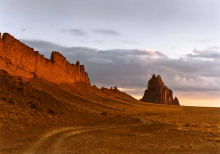 new mexico: A Road to the Fiery Shiprock, New Mexico, Rising From the Desert Plain Just After Dawn