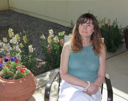 Eine schöne Frau mit langen Haaren sitzt auf einer Terrasse unter Garten-Blumen Standard-Bild - 13698276