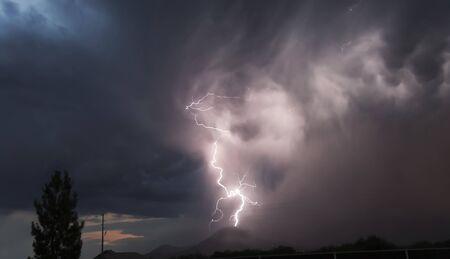 atmospheric phenomena: A Bolt of Lightning Strikes a Distant Mountain Peak