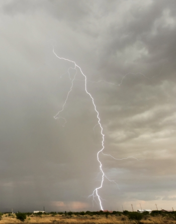 A Bolt of Lightning Strikes a Distant Neighborhood House photo