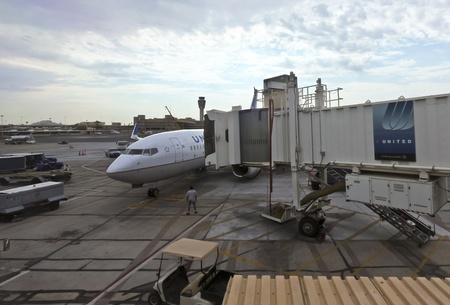 extends: Phoenix, Arizona - July 3: Phoenix Sky Harbor International Airport on July 3, 2012, in Phoenix, Arizona. A jet bridge extends to a commercial United plane waiting on the tarmac. Editorial