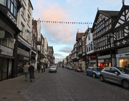 Chester, England - July 11: Bridge Street on July 11, 2012, in Chester, England. Locals and tourists move back and forth on a Bridge Street evening at sunset.