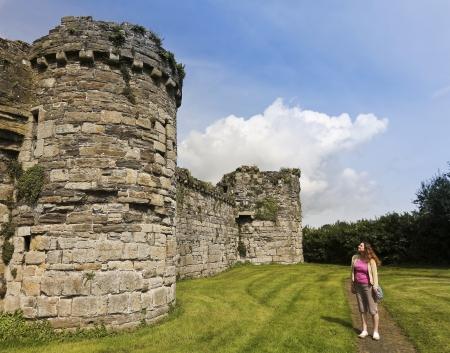 slits: Beaumaris, Wales - July 21: Beaumaris Castle on July 21, 2012, in Anglesey, Wales. A tourist gazes at Beaumaris Castle, a popular tourist destination.