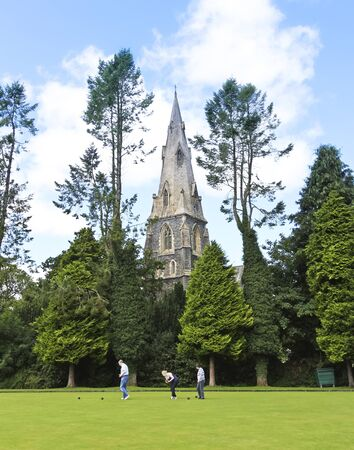 retrieve: Ambleside, England - July 27: St. Marys Church steeple on July 27, 2012, in Ambleside, England. Lawn bowlers retrieve their balls on the green below the steeple of St. Marys Church.