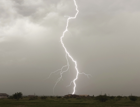 A Lightning Bolt Strikes a Rural Neighborhood House in Arizona During Monsoon Season photo