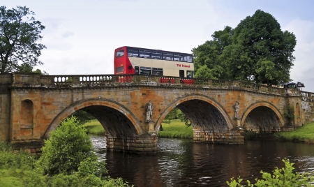 Baslow, England - July 4: An old bridge on July 4, 2012, near Baslow, England. A Double-Decker Bus Crosses an Old Bridge Near Baslow, England, carrying tourists to the famous Chatsworth House.