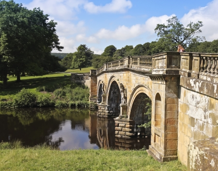 chatsworth: Baslow, England - July 5: An old bridge on July 5, 2012, near Baslow, England. A woman on an old bridge near Baslow, England, popular with tourists visiting the famous Chatsworth House. Editorial