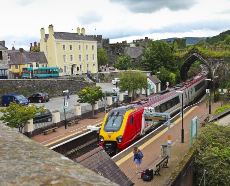 Conwy, Wales - July 18: Conwy Train Station on July 18, 2012, in Conwy, Wales. A woman waits for an approaching train in Conwy, Wales, a popular tourist destination. Stock Photo - 15944815
