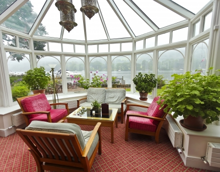 sunroom: A lake View from a Lovely Glass Sitting Room on a Rainy Day Editorial