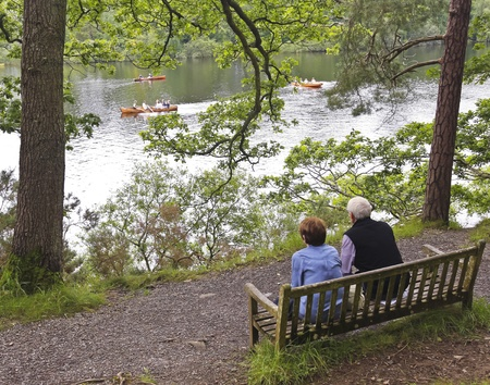 cumbria: Derwentwater, England - July 25: Derwentwater on July 25, 2012, in Cumbria, England. An elderly couple watch people row boats in Derwentwater, popular with tourists. Editorial
