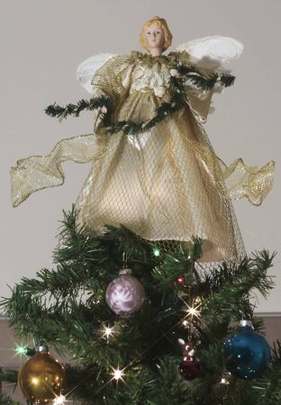 topper: A Christmas Angel Stands Atop a Decorated Christmas Tree