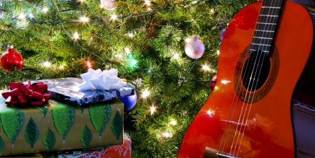 A Red Classical Guitar and Presents Under the Christmas Tree photo
