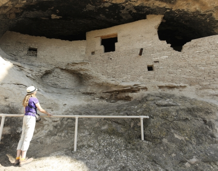 cave dweller: A Woman look at a Rock Face at Gila Cliff Dwellings