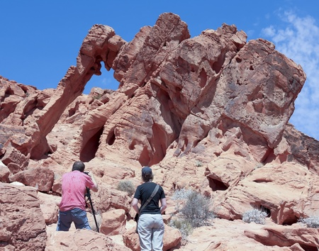 las vistas: OVERTON, NEVADA - JULY 25: The Valley of Fire State Park on July 25, 2013, near Overton, Nevada. A tourist couple takes photos with the Elephant Rock formation in the Valley of Fire State Park near Overton, Nevada.