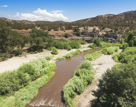 foothill: A Muddy Creek Runs Through a Canyon in the Mountain Foothills Stock Photo