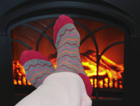 wood stove: A Pair of Feet Warming in Front of a Cozy Fireplace