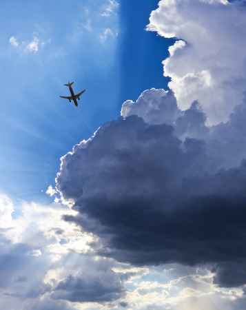 crepuscular: An Airliner in a Blue Sky Full of Cumulus Clouds and Crepuscular Rays Stock Photo