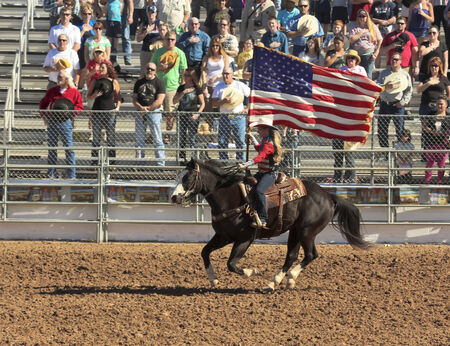 Tucson, Arizona - February 15: The La Fiesta De Los Vaqueros Rodeo on February 15, 2014, in Tucson, Arizona. A horsewomen displays the American Flag at the 89th Annual 2014 Tucson Rodeo.