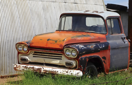 abandoned car: An Old Abandoned Pickup Truck Sits in a Junkyard.         Stock Photo